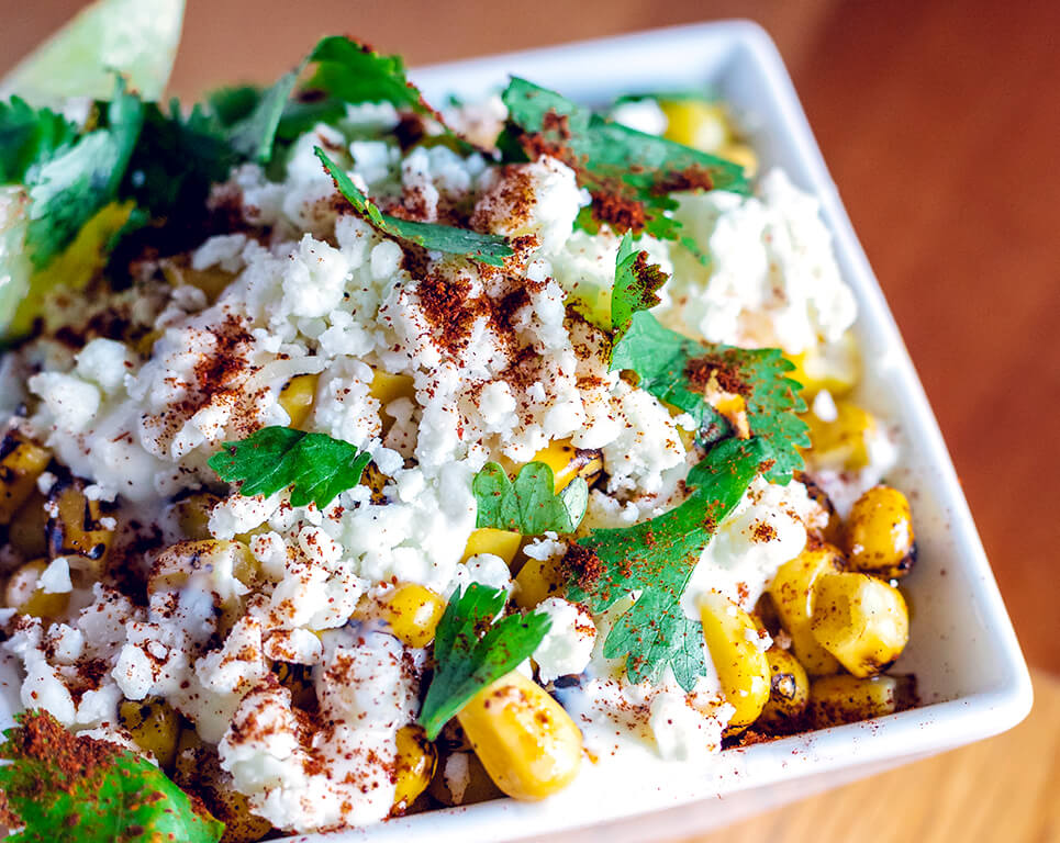 Charred sweet corn, cotija cheese, lime crema, crumbled corn chips, and fresh cilantro