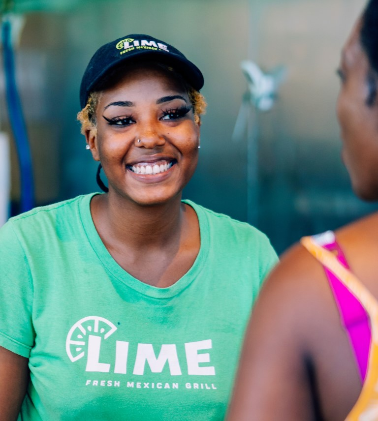 A LIME Fresh Mexican Girl employee smiles at a customer