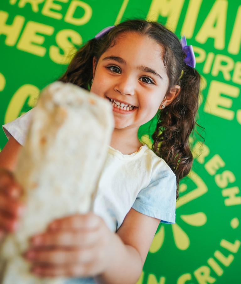 Young girl holds a burrito from LIME Fresh Mexican Grill and smiles
