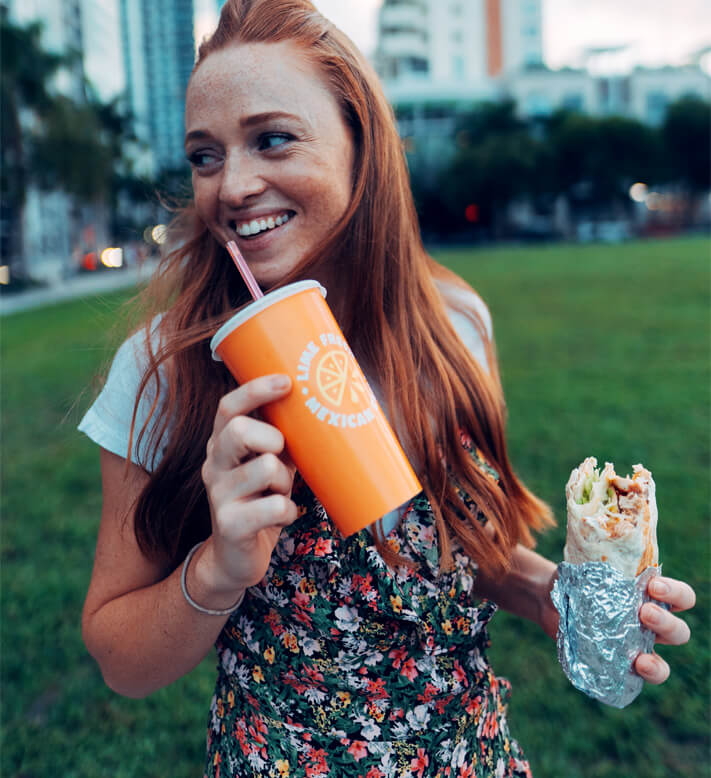 Miami girl posing with LIME Fresh Mexican Grill burrito and drink