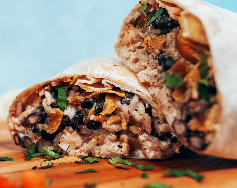 A grilled chicken burrito with rice, lettuce, cheese, bacon, tomato and avocado ranch dressing