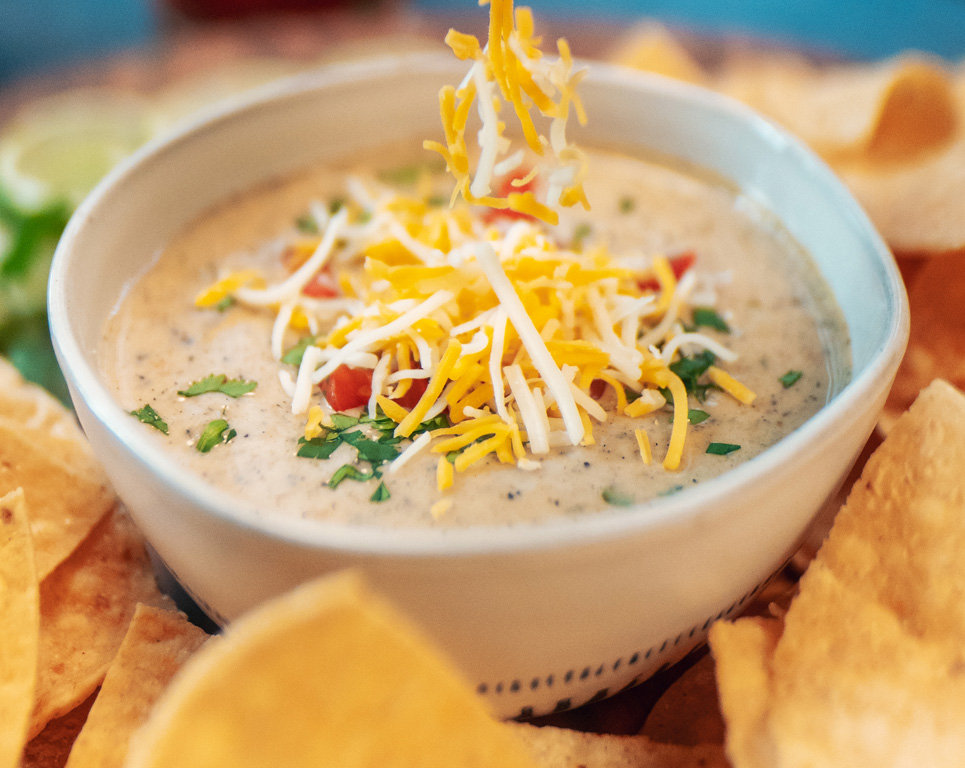homemade queso dip topped with shredded cheese